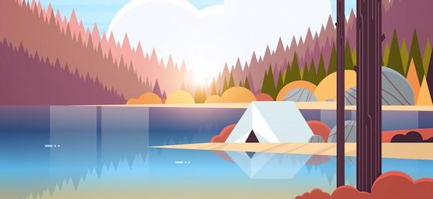 Tienda de campaña en el bosque camping cerca del río otoño campamento viajes vacaciones concepto amanecer paisaje naturaleza con agua montañas y colinas