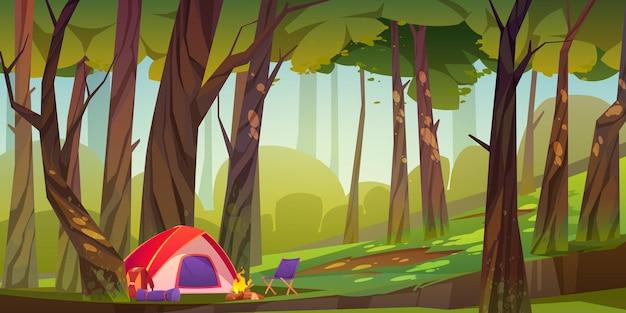 Tienda de campaña con fogata y cosas turísticas en el bosque.