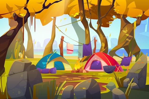 Tiendas de campaña con fuego y cosas turísticas en el bosque de otoño