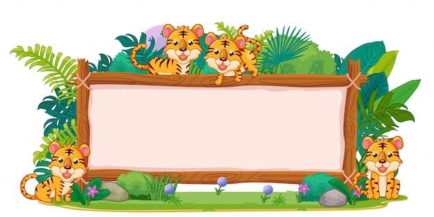 Tigres con un cartel de madera en blanco.