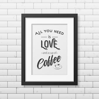 Todo lo que necesitas es amor y una taza de café: cita tipográfica en un marco cuadrado negro realista en la pared de ladrillo.