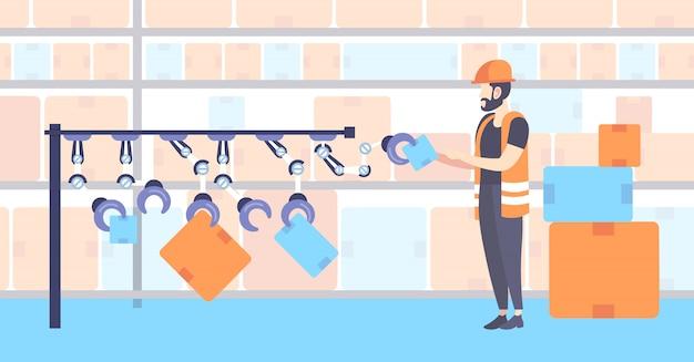 Trabajador de almacén en uniforme arreglando cajas de cartón con brazos de robot línea de producción robótica automatizada interior de almacenamiento moderno de longitud completa horizontal