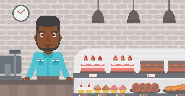 Trabajador de pie detrás del mostrador en la panadería.