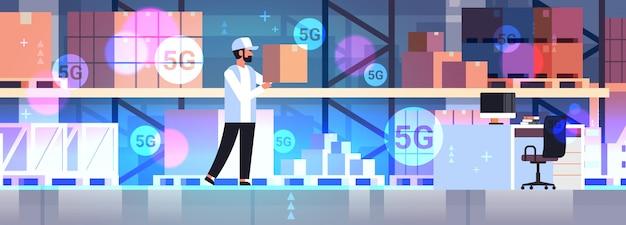 Trabajador que lleva la caja de cartón concepto de comunicación inalámbrica en línea moderno almacén interior horizontal de longitud completa