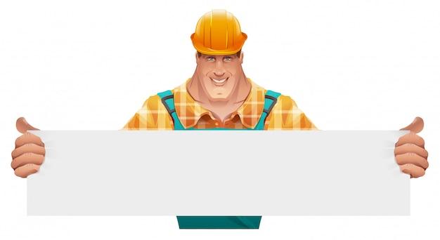 Trabajador de sexo masculino fuerte que sostiene la bandera en blanco. hombre de overol. trabajador en casco