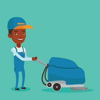 Trabajador de sexo masculino que limpia el piso de la tienda con la máquina.