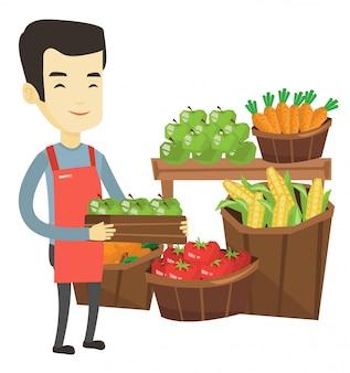 Trabajador de supermercado con caja llena de manzanas.