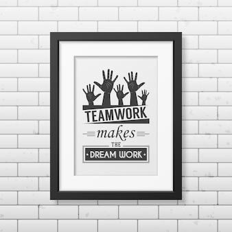 El trabajo en equipo hace que el sueño funcione - cita fondo tipográfico en un marco cuadrado negro realista en el fondo de la pared de ladrillo.