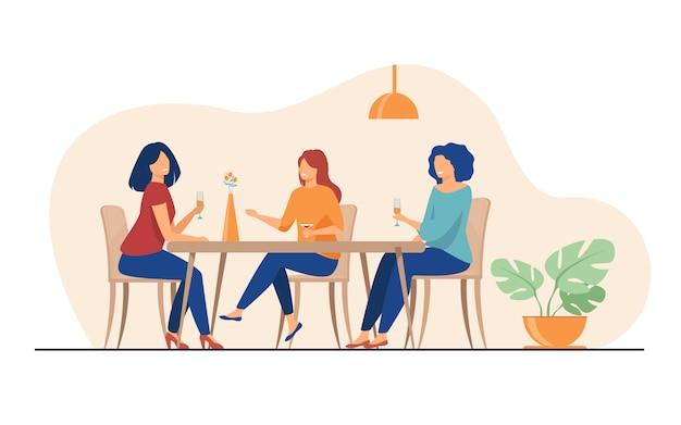 Tres amigas sentadas en la cafetería almorzando y hablando