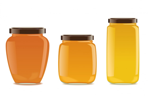 Tres frascos de vidrio con mermelada o miel.