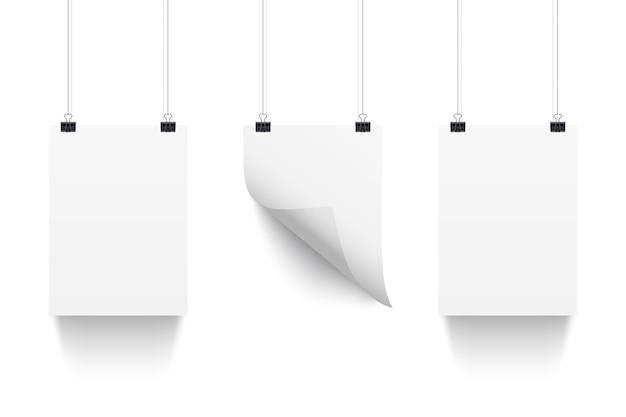 Tres hojas de papel blanco colgando de clips de papel aisladas sobre fondo blanco.