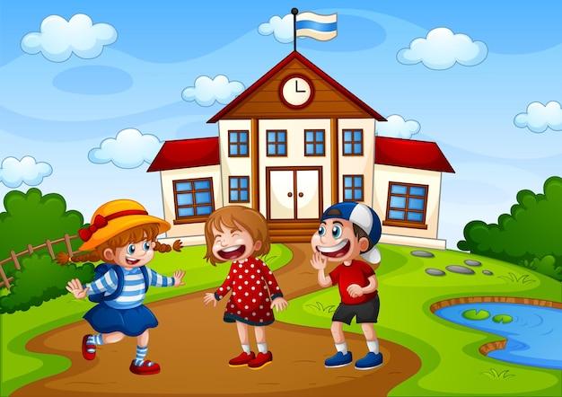 Tres niños en la escena de la naturaleza con edificio escolar.
