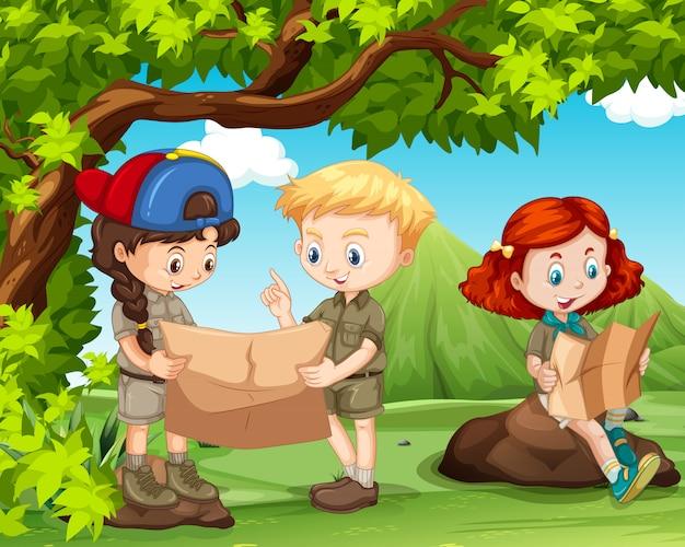 Tres niños leyendo mapas en el campo.