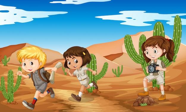 Tres niños en traje de safari corriendo en el desierto