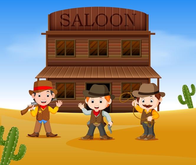 Tres vaqueros sosteniendo arma y parado afuera