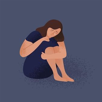 Triste llorando mujer joven solitaria sentada en el suelo. niña infeliz deprimida.