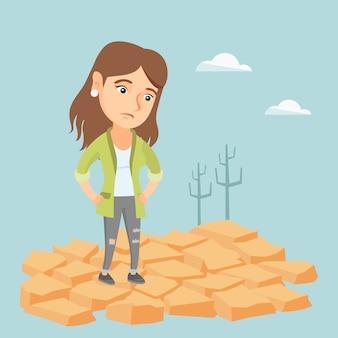 Triste mujer de pie en la tierra agrietada en el desierto.