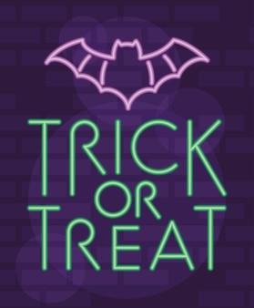 Truco o trato de letras de halloween en luz de neón con murciélago volando