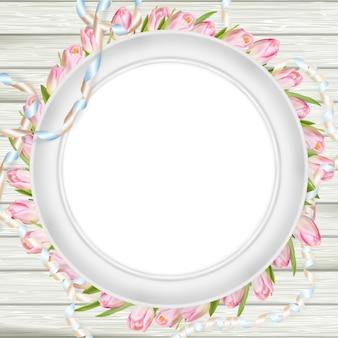 Tulipanes y marco blanco en blanco.