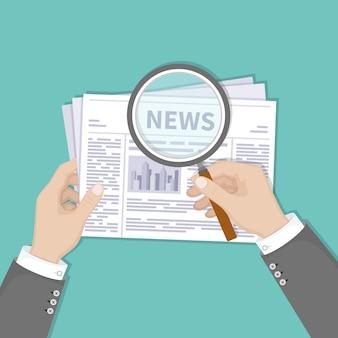 Últimas noticias calientes. manos de empresario sosteniendo lupa sobre un periódico con títulos y fotos. vista superior.
