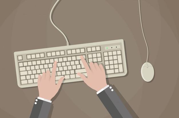 Usuario manos en el teclado y el mouse de la computadora.