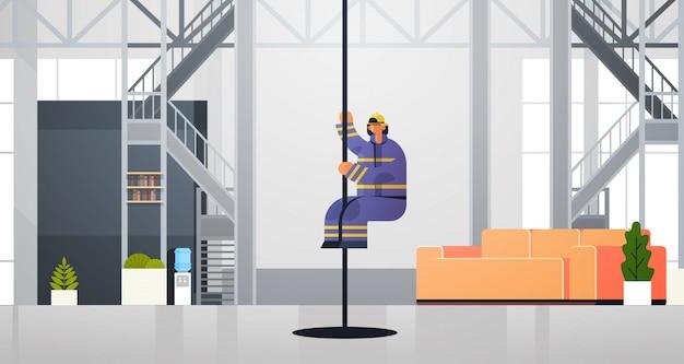 Valiente bombero deslizándose por el poste bombero vistiendo uniforme y casco contra incendios concepto de servicio de emergencia moderno departamento de bomberos interior plano horizontal de cuerpo entero