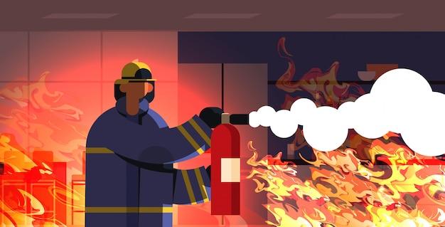 Valiente bombero usando extintor bombero en uniforme y casco contra incendios concepto de servicio de emergencia interior de la casa ardiente llama naranja retrato