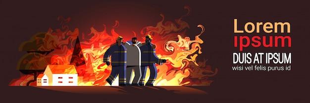 Valiente pareja de bomberos rescatando a un hombre herido de la casa en llamas equipo de bomberos en uniforme servicio de emergencia de extinción de incendios concepto de llama plana espacio completo copia espacio horizontal
