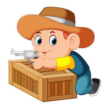 Vaquero inteligente sosteniendo su arma y detrás de la caja.