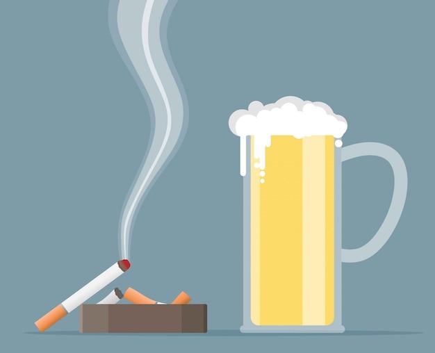 Vaso de cerveza con cigarrillo y cenicero.