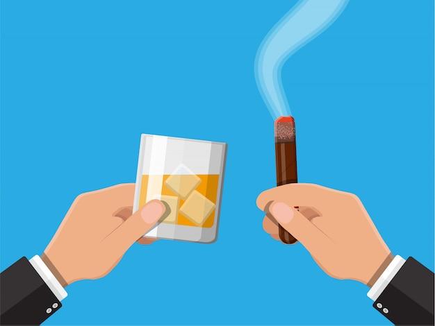 Vaso de whisky con cigarro en mano.