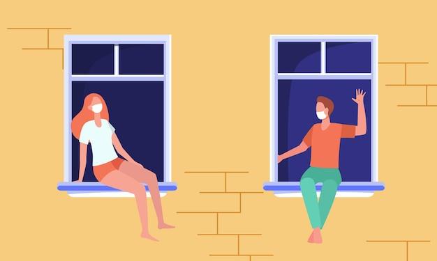 Vecinos con máscaras sentados por separado en los alféizares de las ventanas y charlando. vista de la pared y las ventanas del edificio al aire libre