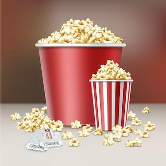 Vector dos cubos a rayas blancas y rojas de granos de palomitas de maíz con entradas de cine de cerca vista lateral sobre fondo borroso