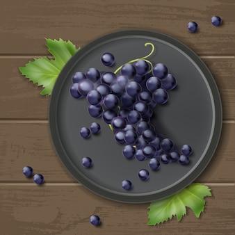 Vector racimo de uvas en placa con hojas, aislado sobre fondo de madera, vista superior