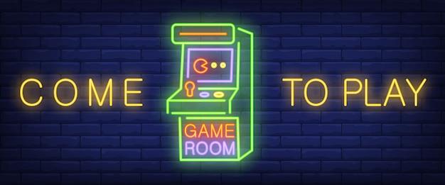 Ven a jugar, texto de neón en la sala de juegos con máquina de juegos de arcade.