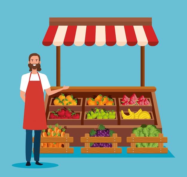 Vendedor con delantal y frutas y verduras saludables.