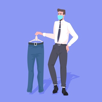 Vendedor con máscara que muestra ropa concepto de cuarentena pandémica de coronavirus