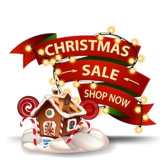 Venta de navidad, banner de descuento en forma de cinta roja, guirnalda envuelta alrededor de la cinta y casa de pan de jengibre de navidad. banner de descuento aislado
