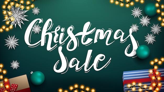 Venta de navidad, banner de descuento verde con hermosas letras, guirnaldas, bolas verdes, regalos y copos de nieve de papel, vista superior