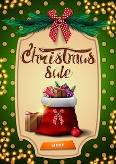 Venta de navidad, banner de descuento vertical verde con bolsa de santa claus con regalos