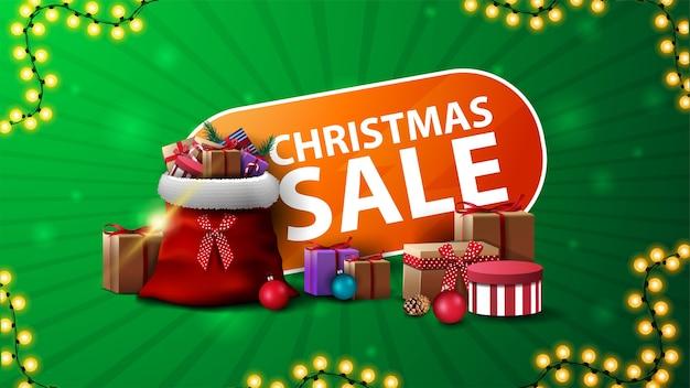 Venta de navidad, banner web de descuento verde y naranja con bolsa de santa claus con regalos