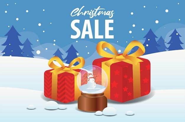 Venta de navidad con bola de cristal y caja de regalo en fondo de paisaje de invierno