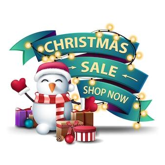 Venta de navidad, compre ahora, banner de descuento en forma de cintas verdes envueltas en guirnalda con muñeco de nieve en sombrero de santa claus con regalos