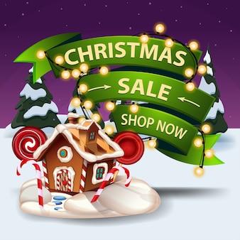 Venta de navidad, compre ahora, banner de descuento con guirnalda envuelta en cinta volumétrica, paisaje invernal y casa de jengibre navideña