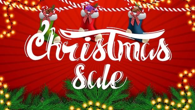 Venta de navidad, hermoso banner de descuento rojo con ramas de árboles de navidad, guirnaldas y medias de navidad