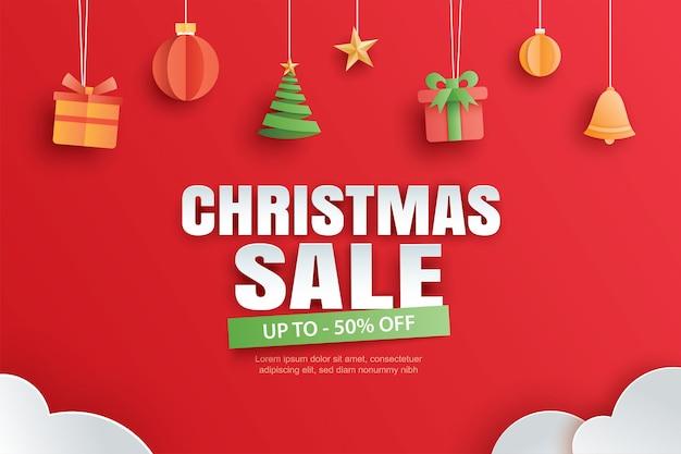 Venta de navidad con regalos y elementos colgados en banner de fondo rojo en estilo de arte de papel.