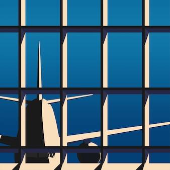 La ventana del aeropuerto con el avión está saliendo de la terminal al atardecer / sol con algo de sombra en tono oscuro cálido