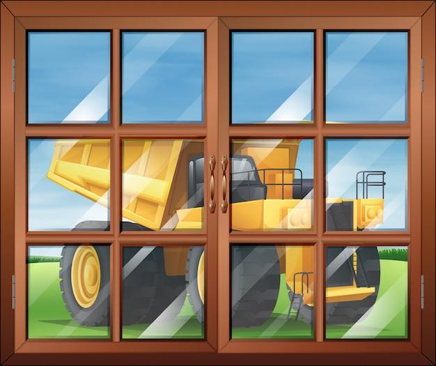Una ventana cerca del vehículo amarillo.