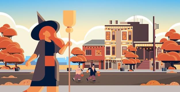 Vestida de bruja espantapájaros disfraz mujer de pie con escoba trucos y convite feliz celebración de fiesta de halloween concepto edificios de la ciudad paisaje exterior