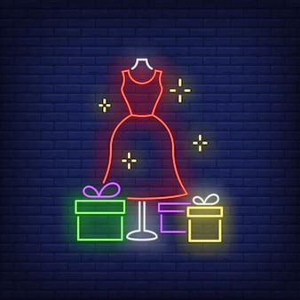 Vestido rojo en maniquí y cajas de regalo de neón